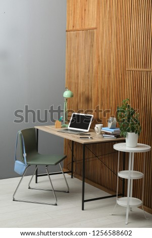 Stylish workplace interior with laptop on table near wooden wall. Space for text #1256588602