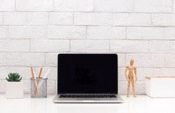 Stylish workplace. Laptop with blank screen and wooden mannequin over white bricks wall, copy space