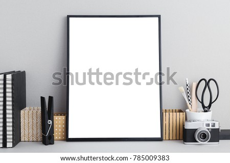 Stylish workspace with black empty photo frame for a poster, stationery, books and a copy space. Mock up