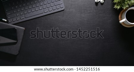 Stylish workspace with laptop and smartphone on black leather office table