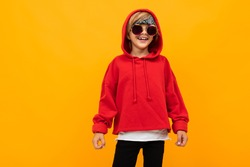 Stylish young boy in red sweatshirt and white t-shirt puts hands on his chest