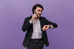 Stylish young brunette-haired businessman in light shirt and striped suit considering time by phone, looking at watch. Busy man posing isolated on violet background