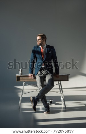 stylish young businessman in formal wear sitting on table and looking away