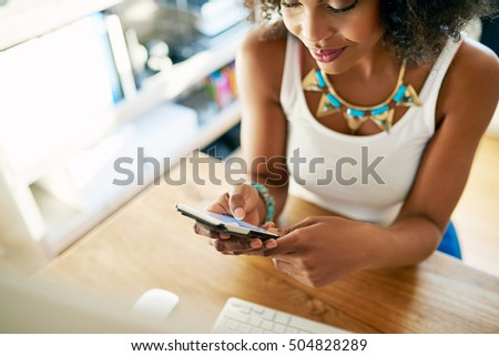 Stylish young businesswoman checking her mobile phone for text messages as she sits at her desk in an office, close up high angle cropped view