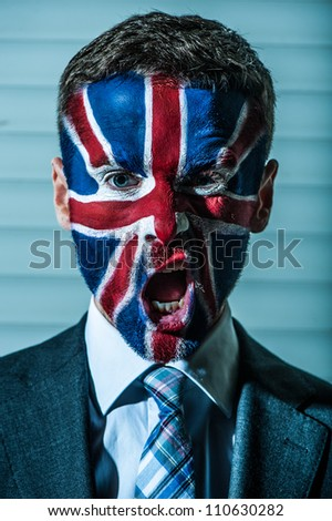 Stylish young coucosian man with emblem of Great Britain on his face. Outdoor night portrait with face art.
