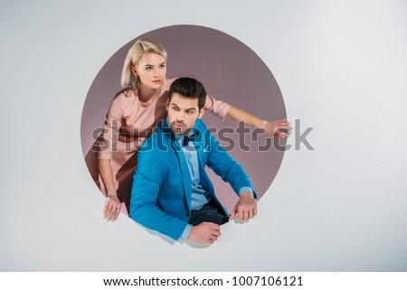 stylish young couple peering out hole on grey