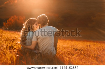 Stylish young couple sitting on a hill and admiring the sunset. A film photo with a light and a sunlight, a foreshortening from the back. Enamored youth in the second before the kiss #1145153852