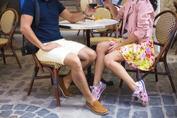Stylish young couple walking on european autumn streets , have fun and hugging. Wearing trendy season outfit. Creamy warm colors.Male and female legs during date,Young couple sitting on ground summer