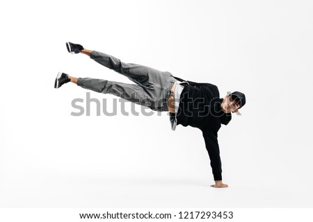 Stylish young dancer is dancing breakdance. He is standing on one arm and lifting both legs up. #1217293453