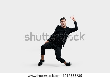 Stylish young dancer wearing a black sweatshirt and black pants makes stylized movements of  hip-poh #1212888235