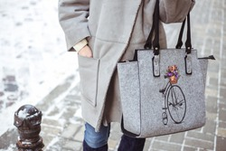 Stylish young fashionable woman with big gray felt bag and deep blue winter boots. Winter street fashion look