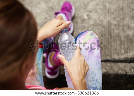 Stylish young female athlete in sportswear holding plastic bottle of drinking water, opening it, preventing dehydration while sitting outdoors after active workout. Selective focus on woman's hands