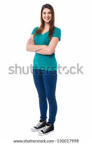 Stylish young female posing before the camera with folded arms, bright smile.