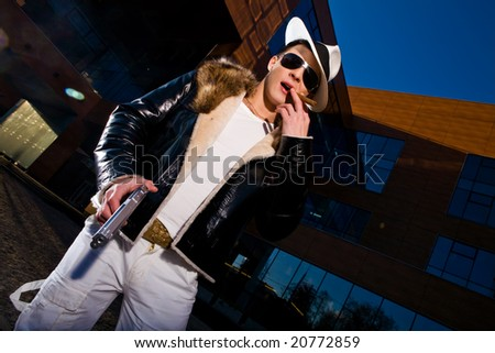 Stylish young gangster standing with a gun and cigar outdoors