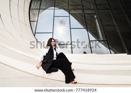 stylish young girl in a black suit posing against the background of an unusual modern building in Baku