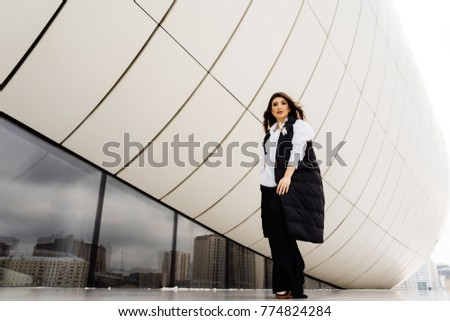 stylish young girl in a black suit posing near an unusual building in Baku