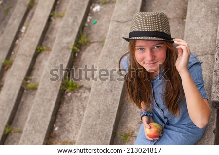 Stylish young girl wearing a hat sitting on stone steps in a park.