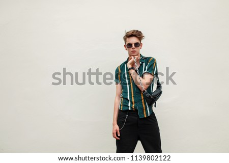 Stylish young handsome man with sunglasses in beach colored shirt with bag posing near green wall