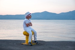 Stylish young hipster sitting on moorage waiting for ship. Little boy dressed in white clothes and hat sitting by the sea. Waiting background. Traveling concept Vacation Holiday Leisuretime Recreation
