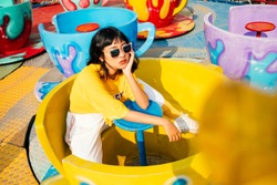 Stylish young hipster woman in stylish in a trendy yellow t-shirt sitting on big cup in Amusement Park. Asian girl enjoys a bright summer sunset.