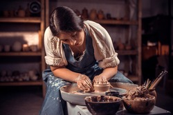Stylish young lady demonstrates the process of making ceramic dishes using the old technology. Handiwork.