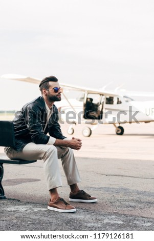 b1987103214 stylish young male pilot in sunglasses sitting on bench near plane