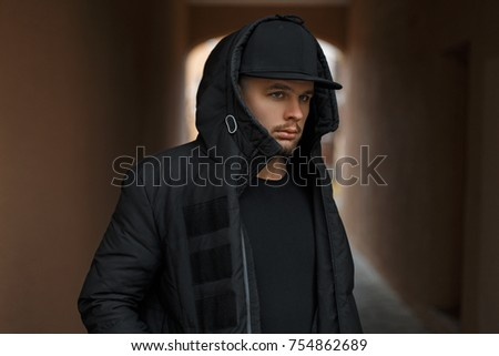 e4712444964 Stylish young man in a baseball cap in a black winter warm jacket with a  hood