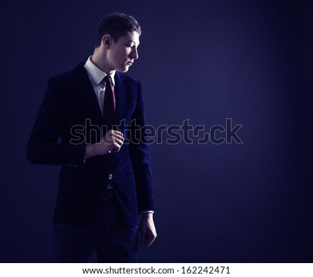 Stylish young man in a blue suit and red tie.