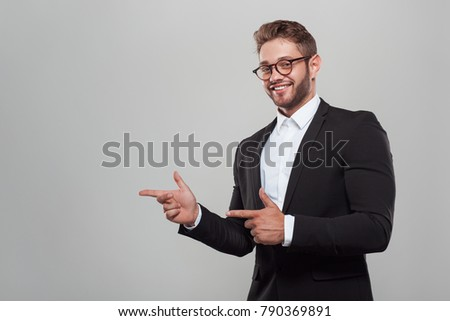 Stylish young man in black suit and eyeglasses pointing away while smiling at camera.