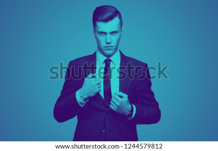 Stylish young man in suit and tie. Business style. Fashionable image. Office worker. Sexy man standing and looking at the camera. Ceremonial clothes. Secular person. Hipster look. Overlay color #1244579812