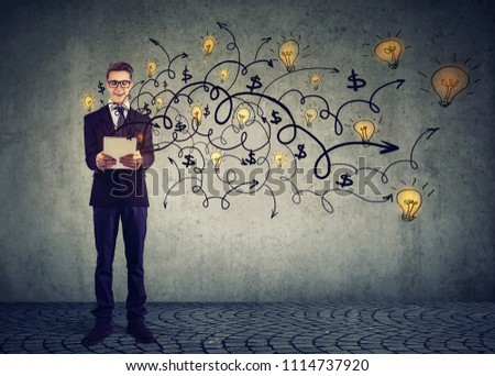 Stylish young man in suit using tablet and spreading plenty of news ideas with creativity on gray background