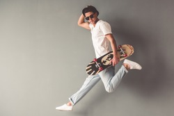 Stylish young man in sun glasses and hat is holding a skateboard and looking at camera while jumping on gray background
