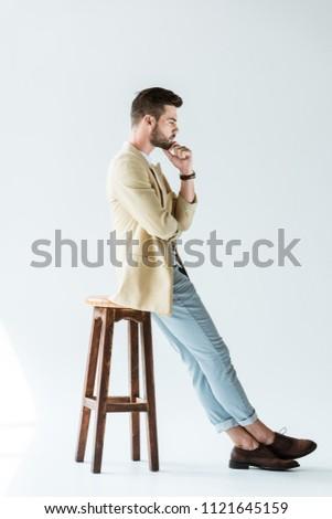 Stylish young man thinking while sitting on stool on white background #1121645159