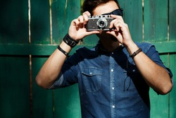 Stylish young man, wearing in blue shirt and sunglasses, holding retro camera in front of his face, with green wooden fence on a background, waist up