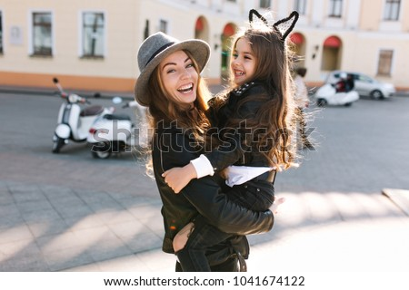 Stylish young mom in retro felt hat carrying her cheerful curly brunette daughter across the street. Portrait of excited girl sitting on mom's hands and looking at her with tenderness