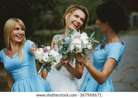 Stylish young smiling blonde bride with her bridesmaids in blue summer dress in the park on her happy  wedding day