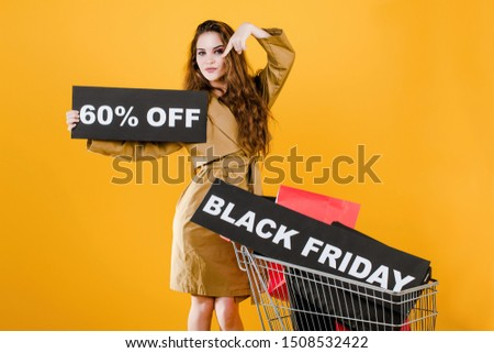 stylish young woman has black friday with 60 discount sign in pushcart with colorful shopping bags and signal tape isolated over yellow
