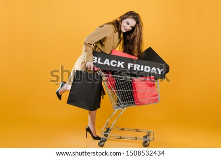 stylish young woman has pushcart and black friday sign with colorful shopping bags and signal tape isolated over yellow