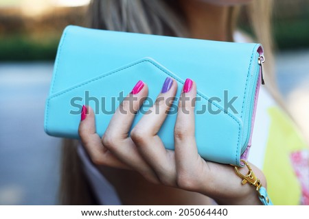 stylish young woman holding blue clutch in hand with pink manicure