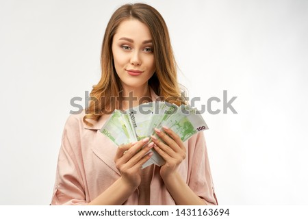Stylish young woman holds large amount of cash in her hand. The concept of financial success, wealth and prosperity. Portrait of young European girl with cash euro in hand and happy joyful expression.