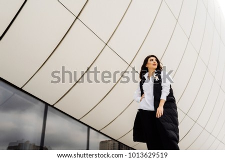 stylish young woman in a black suit posing against the background of the unusual architecture of the city of Baku