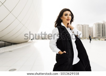 stylish young woman in a black suit posing against the background of the unusual architecture of the city of Baku, smiling