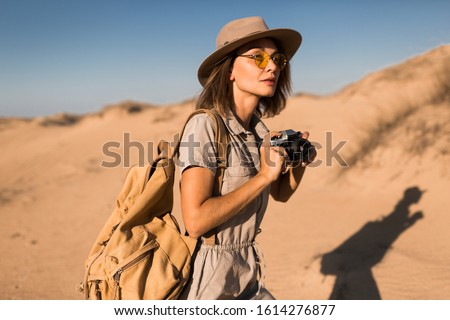 stylish young woman in khaki dress walking in desert sand, traveling in Africa on safari, wearing hat and backpack, taking photo on vintage camera, exploring nature, hot summer day, sunny weather Foto stock ©