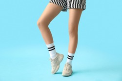 Stylish young woman in shoes and socks on color background
