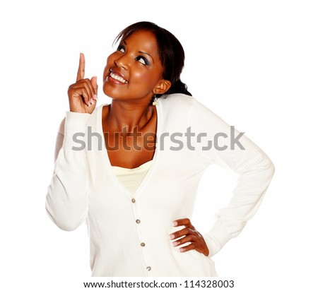 Stylish young woman pointing and looking up against white background
