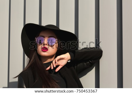 Stylish young woman posing in mirror glasses and broad brimmed hat. Female fashion concept