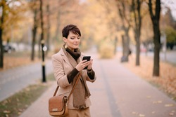 stylish young woman uses smartphone against background of autumn street