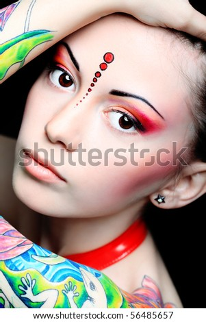 Stylish young woman with colored tattoo on her hand. Shot in a studio.