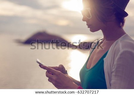 Stylish young woman with mobile phone in hands on the seashore. Communication and roaming during the holidays and travel around the world