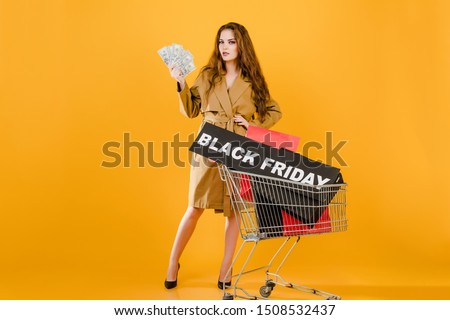 stylish young woman with money has black friday sign in pushcart with colorful shopping bags and signal tape isolated over yellow